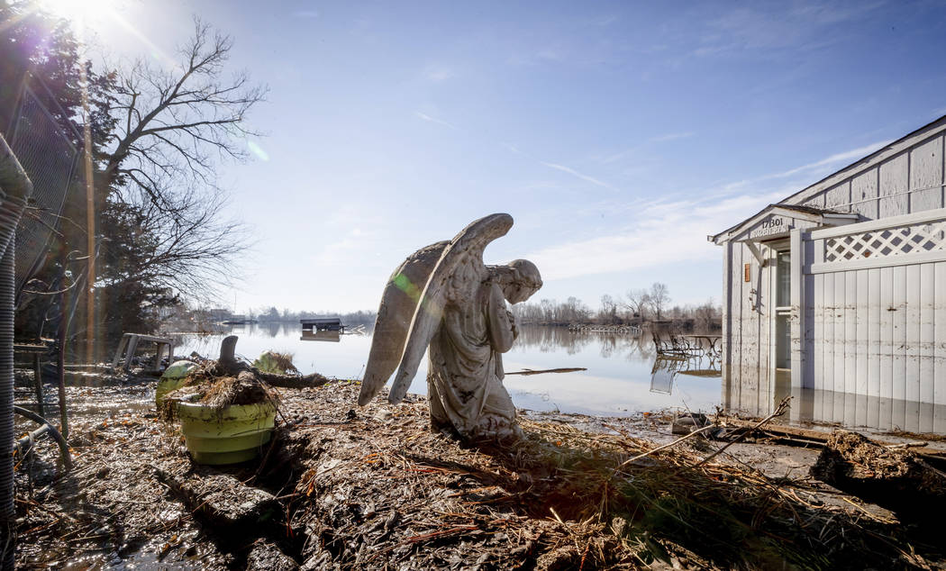 An angel statuary graces a yard near Hansen Lake Friday, March 22, 2019, in Bellevue, Neb. Residents were allowed into the area for the first time since floodwaters overtook several homes. Floodin ...