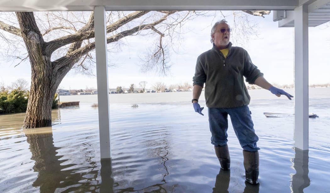 Tim Bazar stands on the back deck of his flooded house Friday, March 22, 2019, in Bellevue, Neb. Flooding in Nebraska has caused an estimated $1.4 billion in damage. The state received Trump's fed ...