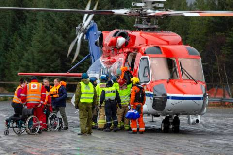Passengers are helped from a rescue helicopter in Fraena, Norway, Sunday March 24, 2019, after being rescued from the Viking Sky cruise ship. Rescue workers are evacuating more passengers from a c ...