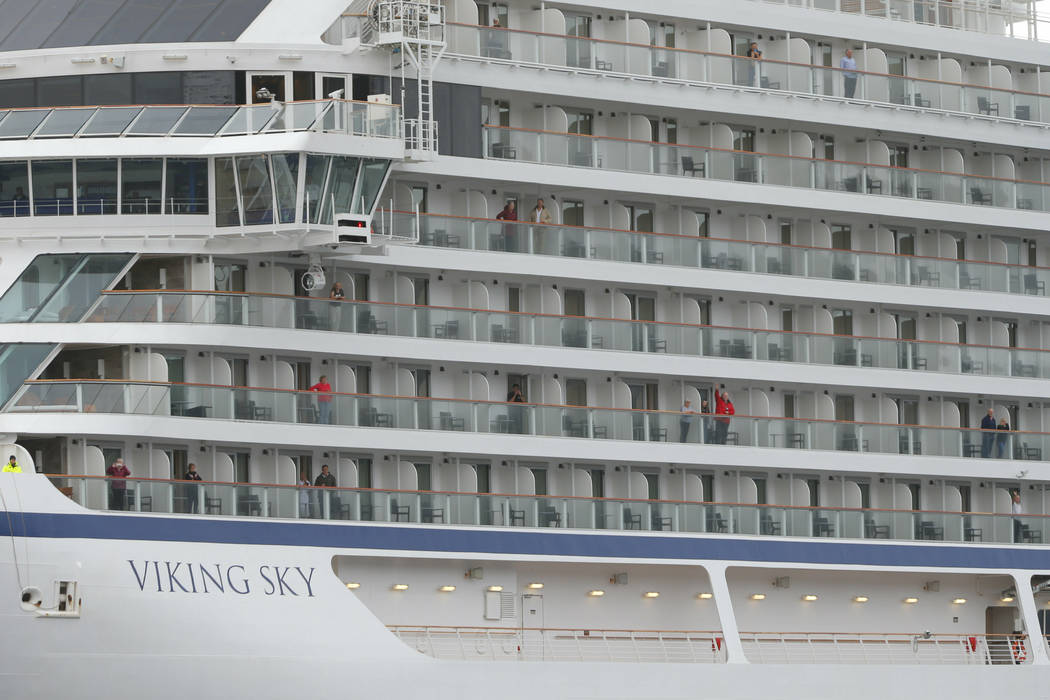 Some of the remaining passengers look out as the cruise ship Viking Sky arrives at port off Molde, Norway, Sunday March 24, 2019, after having problems and issuing a Mayday call on Saturday in hea ...