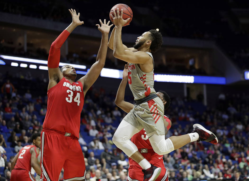Houston's Galen Robinson Jr., right, heads to the basket as Ohio State's Kaleb Wesson (34) defends during the second half of a second round men's college basketball game in the NCAA Tournament Sun ...