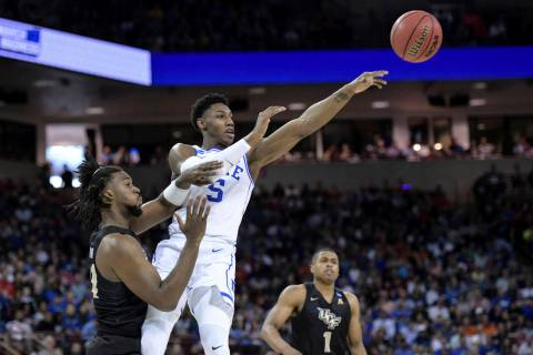 Duke forward RJ Barrett (5) passes to a teammate, away from Central Florida forward Chad Brown, left, during the first half of a second-round game in the NCAA men's college basketball tournament S ...