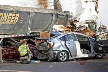 In this Oct. 29, 2013, file photo, Arizona Department of Public Safety officers investigate a multiple fatality accident involving six semi tractor-trailers and 19 other vehicles after a dust stor ...