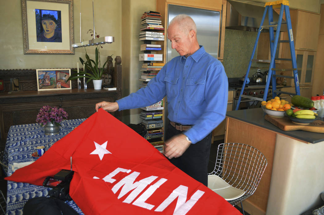 In this Jan. 17, 2019 photo, Todd Greentree, a former U.S. Embassy political officer in El Salvador during its civil war, shows a rebel Farabundo Marti National Liberation Front flag in his Santa ...