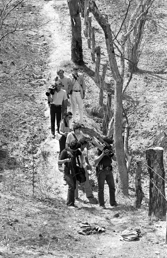 In this March 18, 1982 photo, television cameramen photograph blood-soaked, bullet-ridden clothes believed to belong to four Dutch journalists killed in a wooded area near this village in the prov ...