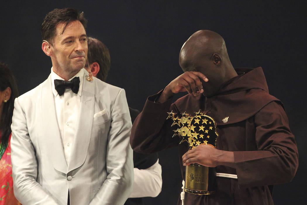 Kenyan teacher Peter Tabichi, right, reacts as actor Hugh Jackman, watches after the teacher won the $1 million Global Teacher Prize in Dubai, United Arab Emirates, Sunday, March 24, 2019. Tabichi ...