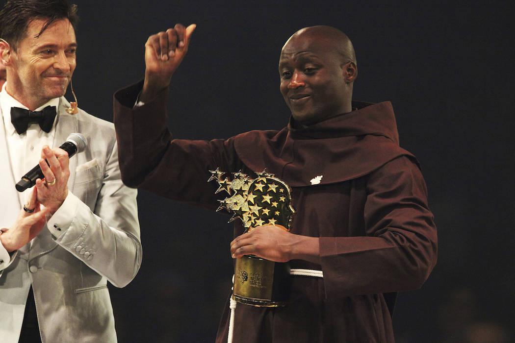 Kenyan teacher Peter Tabichi, right, reacts near actor Hugh Jackman, left, after winning the $1 million Global Teacher Prize in Dubai, United Arab Emirates, Sunday, March 24, 2019. Tabichi is a sc ...