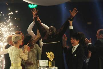Kenyan teacher Peter Tabichi, center, reacts after winning the $1 million Global Teacher Prize in Dubai, United Arab Emirates, Sunday, March 24, 2019. Tabichi is a science teacher who gives away 8 ...