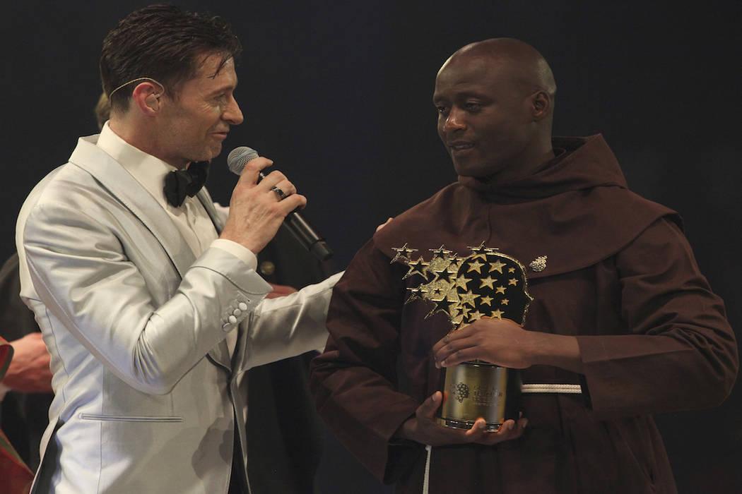 Kenyan teacher Peter Tabichi, right, listens to actor Hugh Jackman, after winning the $1 million Global Teacher Prize in Dubai, United Arab Emirates, Sunday, March 24, 2019. Tabichi is a science t ...