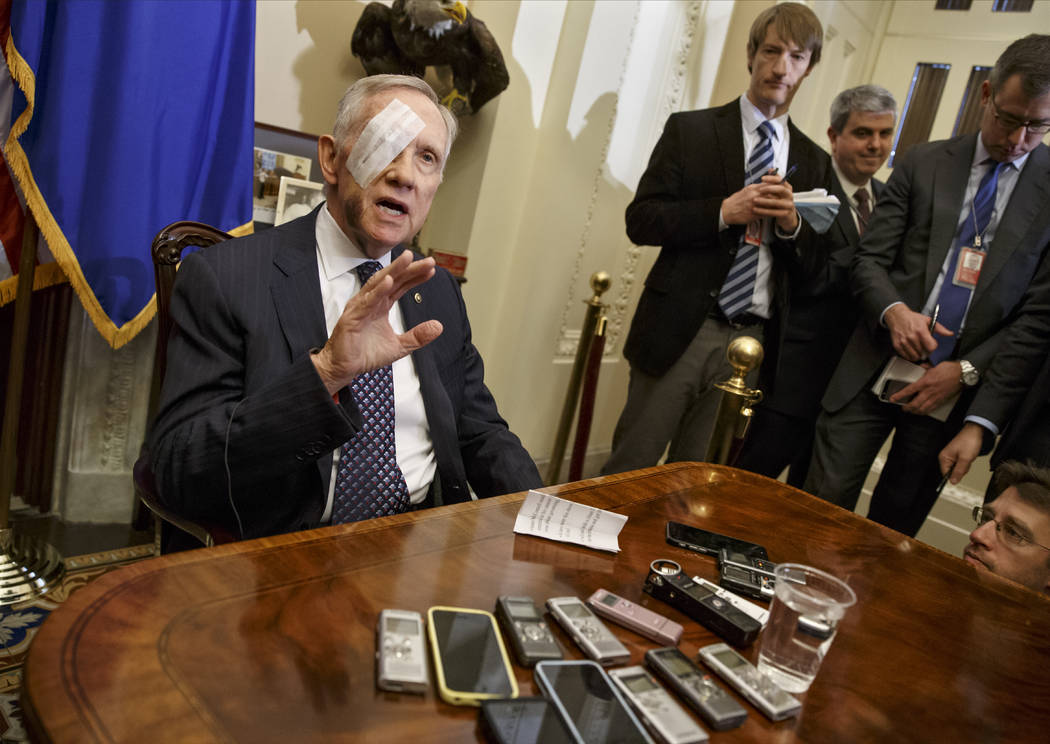 Then-Senate Minority Leader Harry Reid of Nevada talks to reporters on Capitol Hill in Washington, D.C., on Jan. 22, 2015, for the first time after suffering an eye injury and broken ribs during a ...