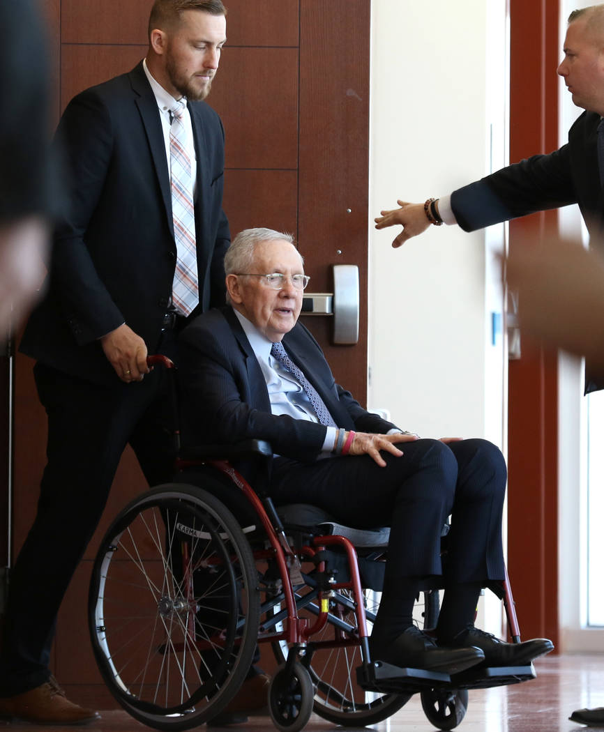 Former U.S. Sen. Harry Reid, who sued the makers of an exercise band after injuring his eye, leaves the courtroom in a wheelchair after attending the first day of jury selection in his civil tria ...