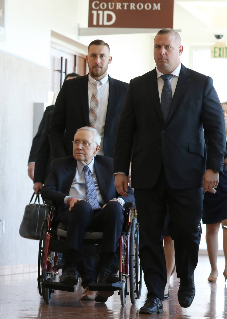 Former U.S. Sen. Harry Reid, who sued the makers of an exercise band after injuring his eye, leaves the courtroom in a wheelchair after attending the first day of jury selection in his civil trial ...