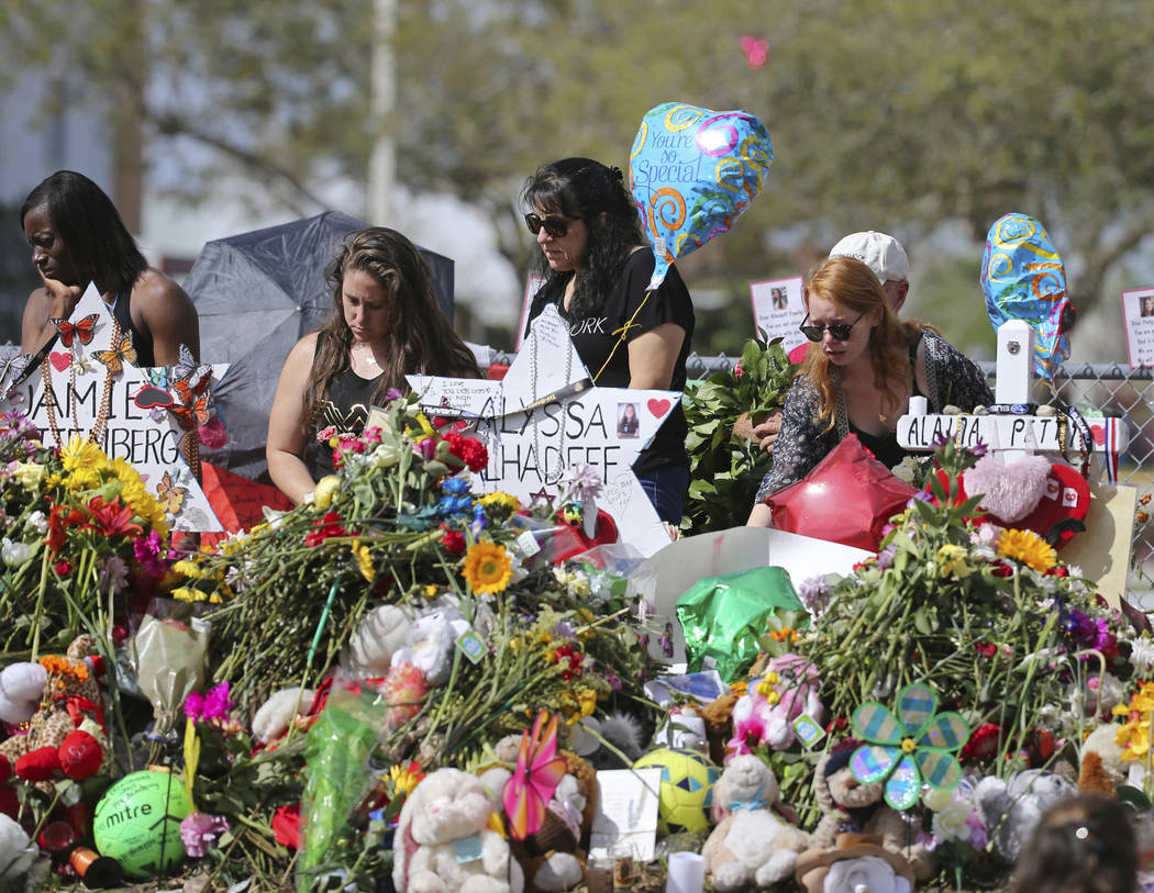 FILE - In this Feb. 25, 2018 file photo, mourners bring flowers as they pay tribute at a memorial for the victims of the shooting at Marjory Stoneman Douglas High School, in Parkland, Fla. The com ...
