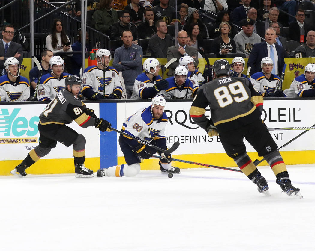 Vegas Golden Knights right wing Alex Tuch (89) skates towards center Jonathan Marchessault (81) and St. Louis Blues center Ryan O'Reilly (90) as they fight for the puck during the first period of ...