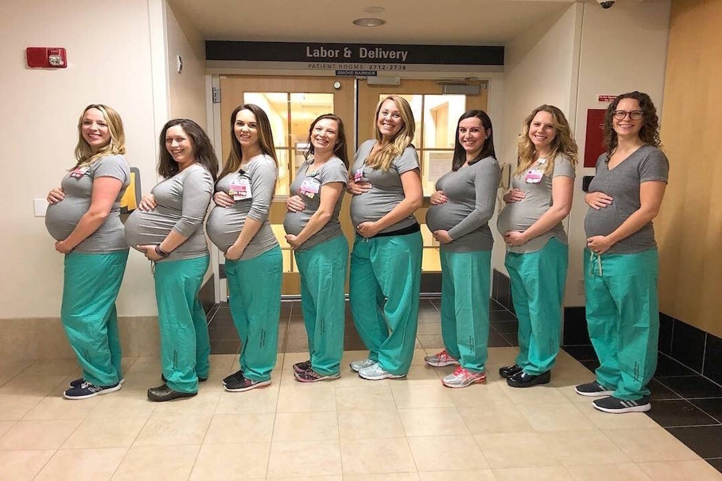 =In this March 23, 2019 photo, eight labor and delivery nurses at Maine Medical Center hold up cards with their due dates in Portland, Maine. Nine nurses at the Portland hospital's labor and del ...
