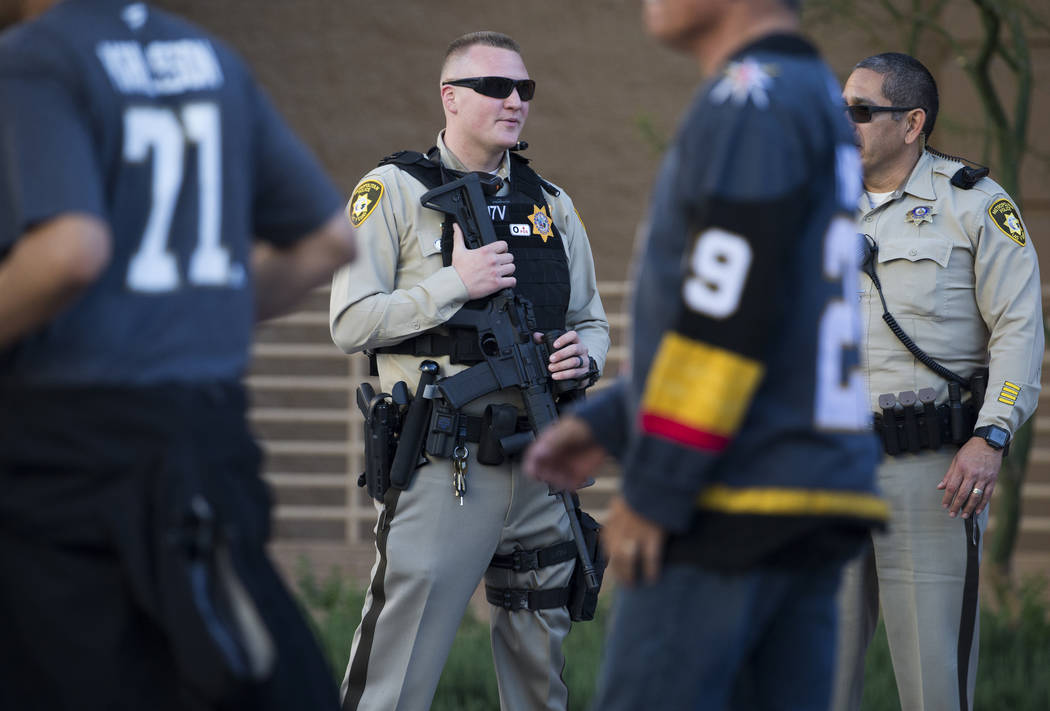 Metro officer Dallin Van Buskirk, left, armed with an AR-15 semi-automatic rifle with a scope, ...