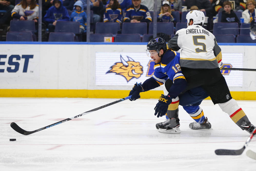 St. Louis Blues' Zach Sanford (12) attempts to maintain control of the puck against Vegas Golden Knights' Deryk Engelland (5) during the second period of an NHL hockey game Monday, March 25, 2019, ...