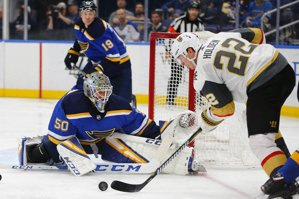 St. Louis Blues' goalie Jordan Binnington (50) looks to make a save against Vegas Golden Knights' Nick Holden (22) during the third period of an NHL hockey game Monday, March 25, 2019, in St. Loui ...