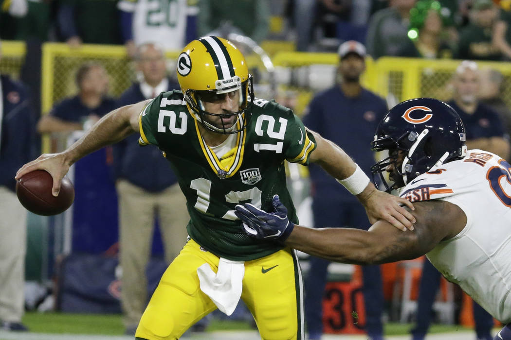 Green Bay Packers' Aaron Rodgers gets away from Chicago Bears' Akiem Hicks during the first half of an NFL football game Sunday, Sept. 9, 2018, in Green Bay, Wis. (AP Photo/Mike Roemer)