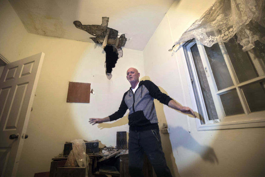 Israeli Shlomo Moskowitz examines the damage to his house after it was hit by a rocket in Sderot, southern Israel, Monday, March 25, 2019. Israeli forces on Monday struck targets across the Gaza S ...