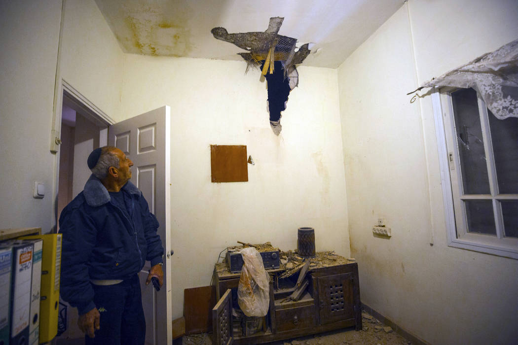An Israeli man examines the damage to a house after it was hit by a rocket in Sderot, southern Israel, Monday, March 25, 2019. Israeli forces on Monday struck targets across the Gaza Strip, includ ...