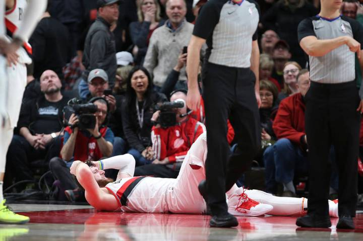 Portland Trail Blazers center Jusuf Nurkic, on ground, was injured and left the court on a stretcher as the Blazers beat the Brooklyn Nets in double overtime, 148-144, during an NBA basketball gam ...