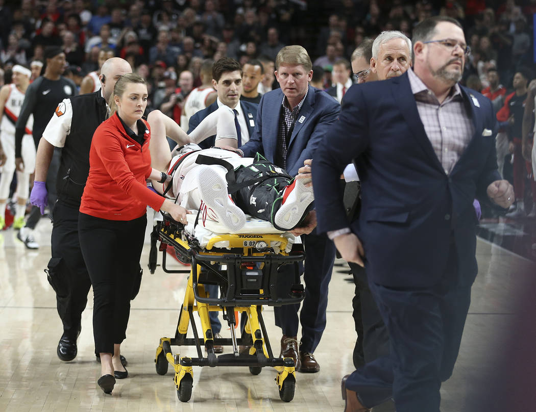 Portland Trail Blazers center Jusuf Nurkic, center, was injured and left the court on a stretcher as the Blazers beat the Brooklyn Nets in double overtime, 148-144, during an NBA basketball game i ...