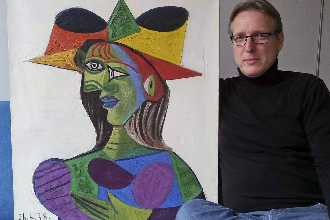 """This image released on Tuesday March 26, 2019, shows Dutch art detective Arthur Brand with """"Buste de Femme"""", a recovered Picasso painting. The painting was stolen from a wealthy Saudi's yacht 20 y ..."""
