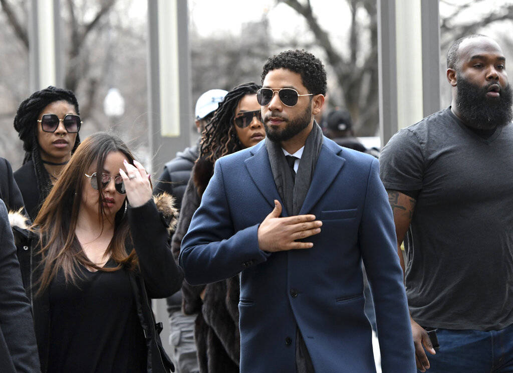 Empire actor Jussie Smollett, center, arrives at the Leighton Criminal Court Building for his hearing on Thursday, March 14, 2019, in Chicago. Smollett is accused of lying to police about being t ...