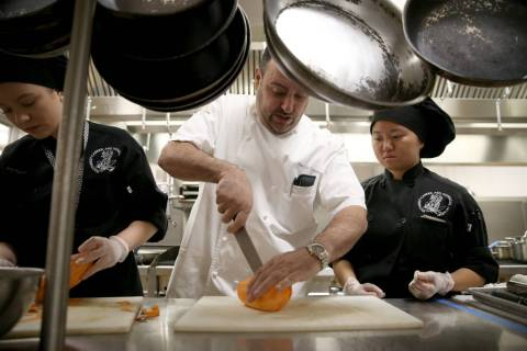 Chef Barry Dakake of Scotch 80 Prime, center, works with culinary arts students including Desti ...