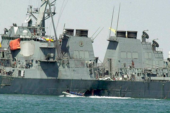 Experts in a speed boat examine the damaged hull of the USS Cole at the Yemeni port of Aden after an al-Qaida attack that killed 17 sailors on Oct. 15, 2000. The Supreme Court on Tuesday threw out ...