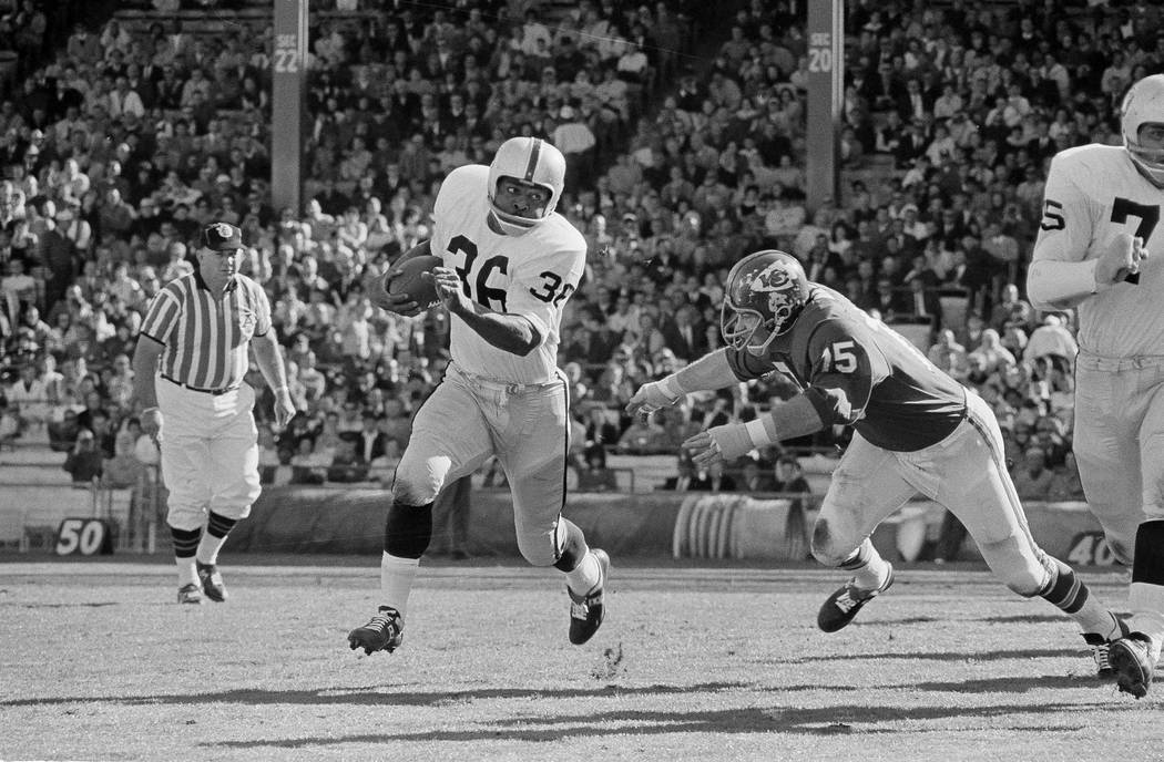 Clem Daniels (36) of the Oakland Raiders races around the right side of his line as Jerry Mays, right, of the Kansas City Chiefs moves in for the tackle, in Kansas City, Mo. on Oct. 31, 1965. (AP ...