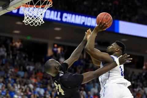 Duke's Zion Williamson, right, shoots over Central Florida's Tacko Fall during the second half of a second-round men's college basketball game in the NCAA Tournament in Columbia, S.C. Sunday, Marc ...