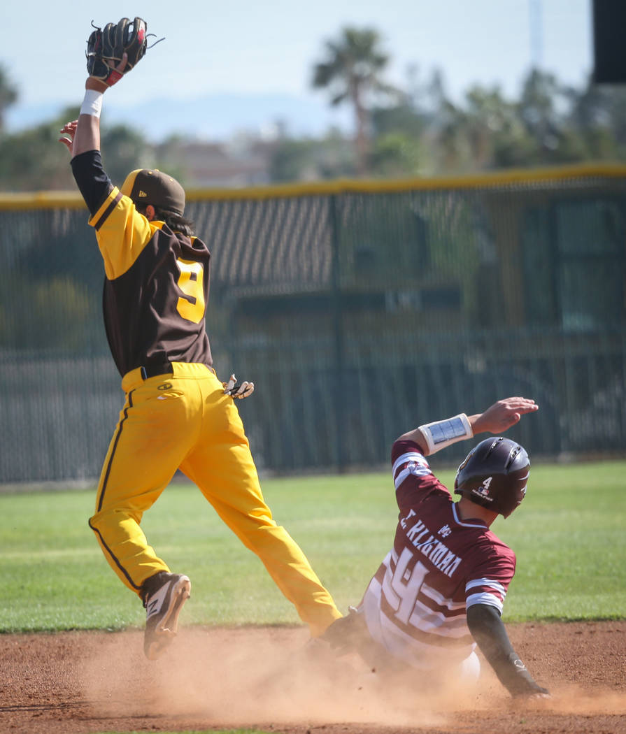 Bonanza second baseman Andre Holloway (9) catches the ball as Cimarron-Memorial infielder Elie Kligman (4) slides into second base during a baseball game at Bonanza High School in Las Vegas, Tuesd ...