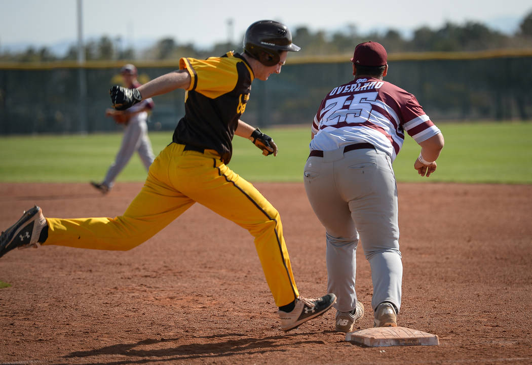 Cimarron-Memorial infielder Mike Overland (25) catches the ball getting out Bonanza first baseman Ryan Webster (19) runs to first base during a baseball game at Bonanza High School in Las Vegas, T ...