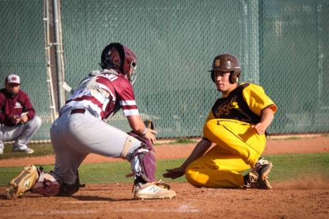 Bonanza shortstop Yankiel Gonzalez (24) slides into home plate as Cimarron-Memorial catcher Will Zadrowski (8) catches the ball to get him out during a baseball game at Bonanza High School in Las ...