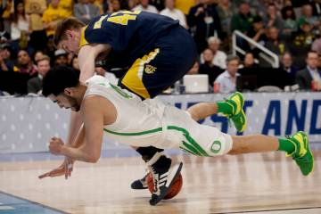UC Irvine forward Tommy Rutherford, top, and Oregon guard Ehab Amin vie for a loose ball during ...