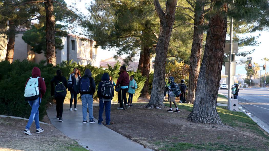 Students wait for the school bus on Soaring Gulls Drive near Cheyenne Avenue at Desert Shores V ...