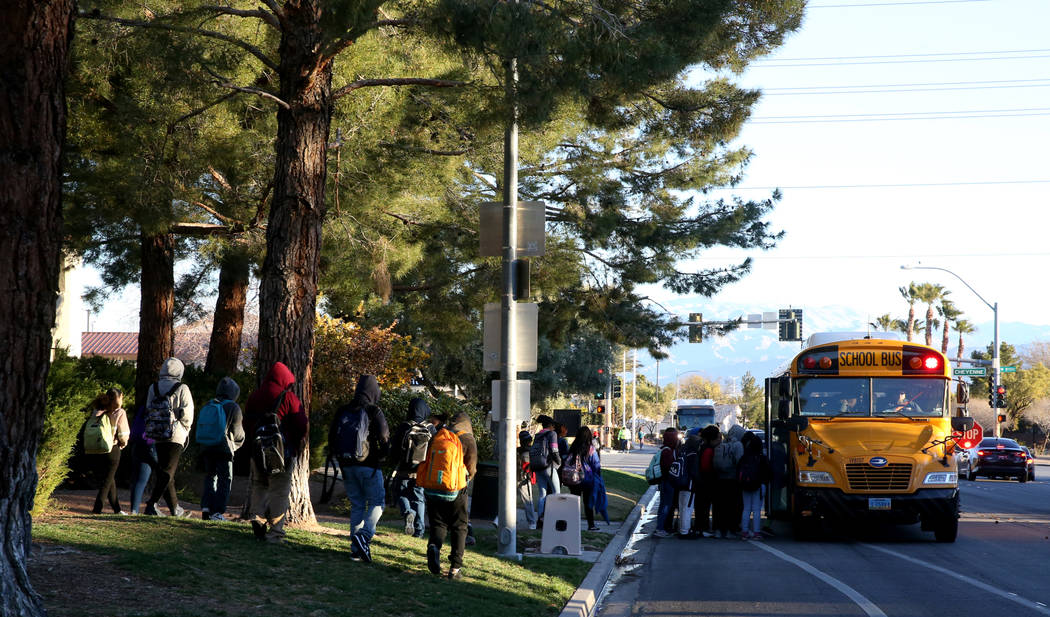 Students board the school bus on Soaring Gulls Drive near Cheyenne Avenue at Desert Shores Vill ...
