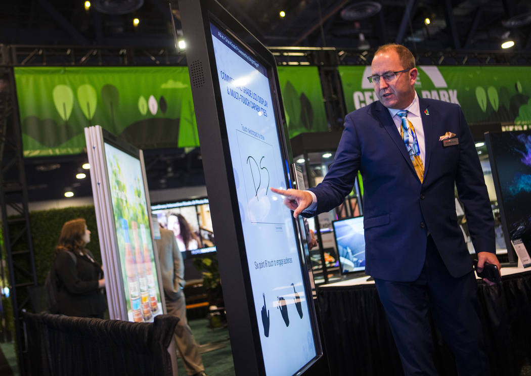 Brian McClimans, vice president of sales at Peerless-AV, shows off an all-in-one digital kiosk ...