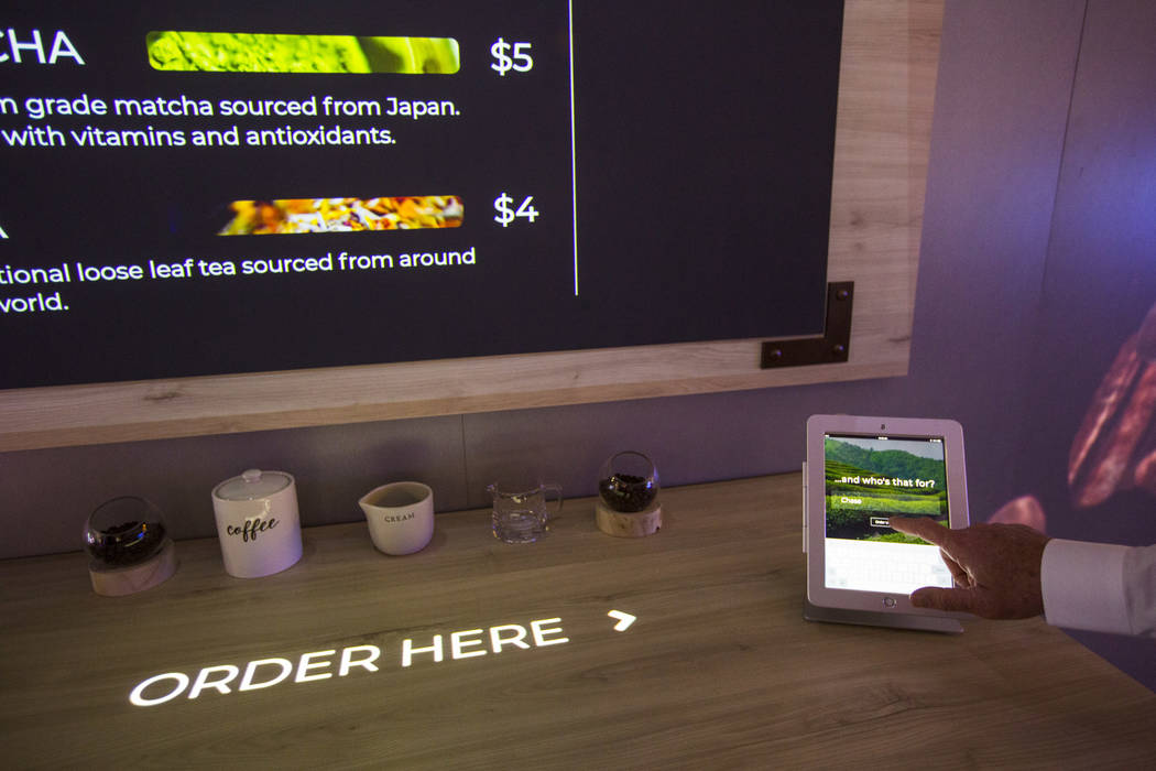 Projected signage is integrated with a digital touch display at the Epson booth at the Digital ...