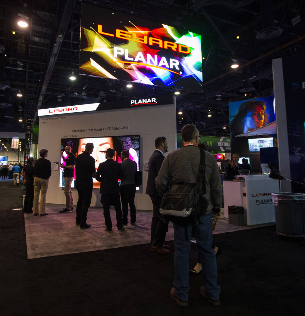 Attendees walk by the Leyard and Planar booth at the Digital Signage Expo at the Las Vegas Conv ...