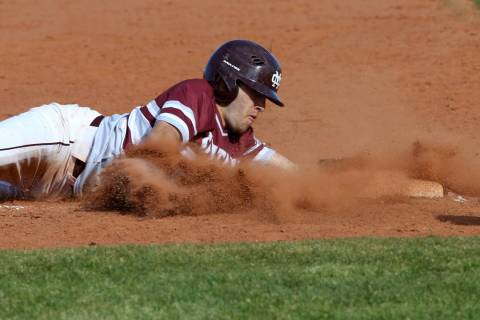 Cimarron-Memorial baserunner Lawrence Campa (15) slides safely into third base in the third inn ...