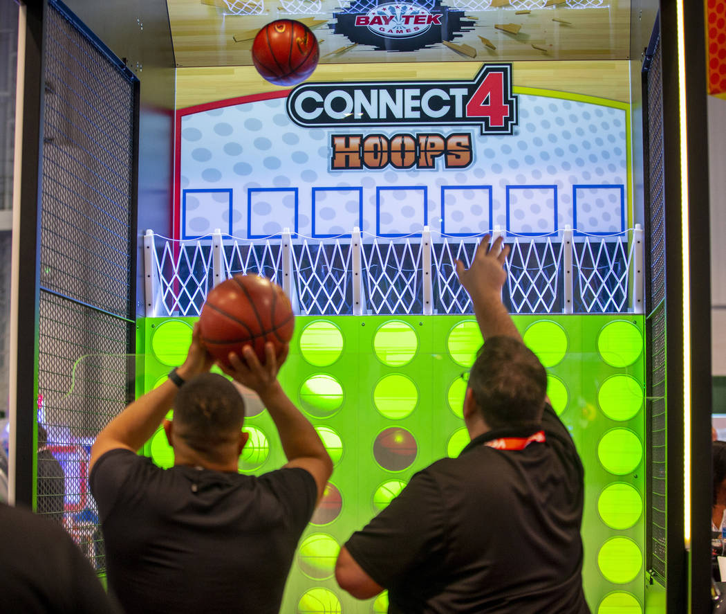 Attendees shoot baskets in a Connect 4 Hoops game during the the Amusement Expo at the Las Vega ...
