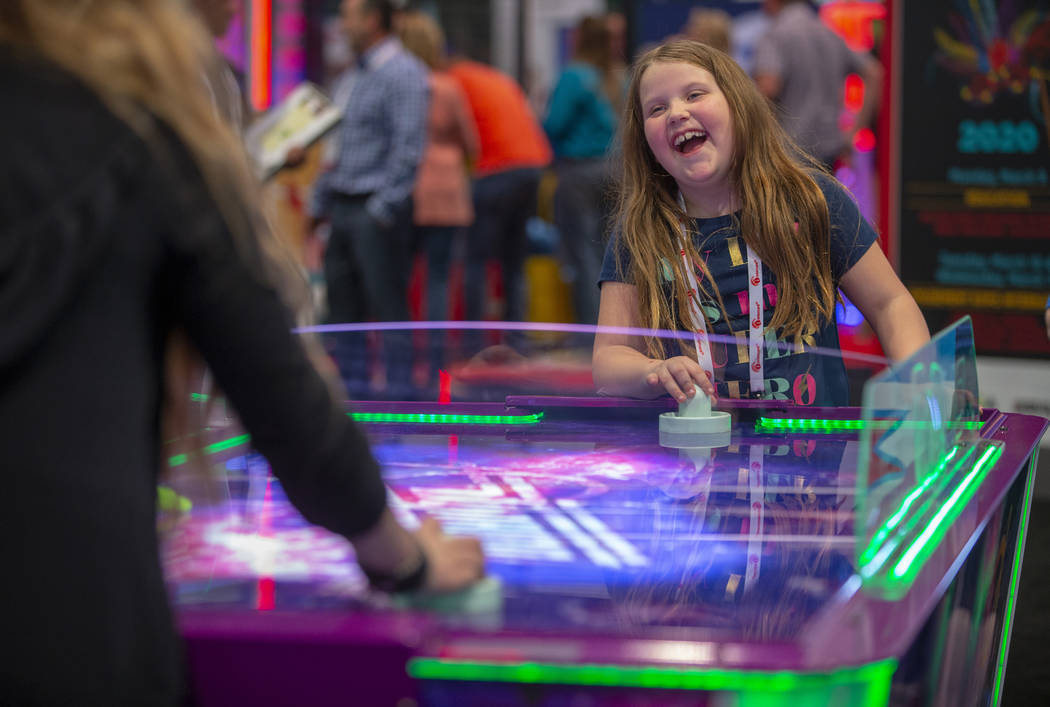 Evva Fortier with Gamepath Arcade plays air hockey with a friend during the the Amusement Expo ...