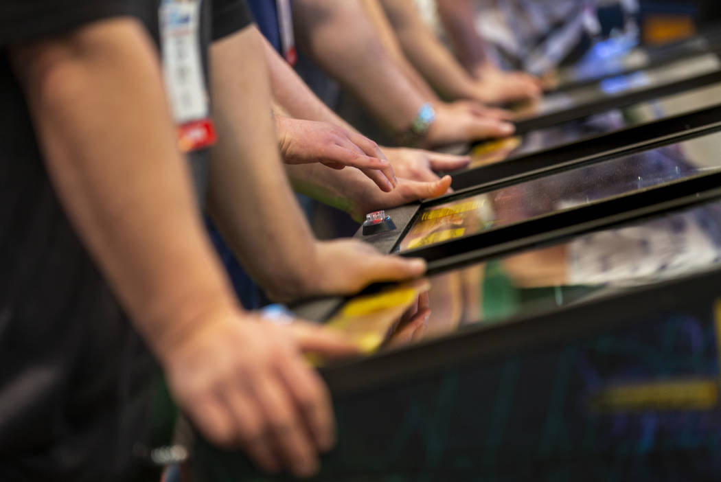 Attendees play pinball during the the Amusement Expo at the Las Vegas Convention Center on Wedn ...