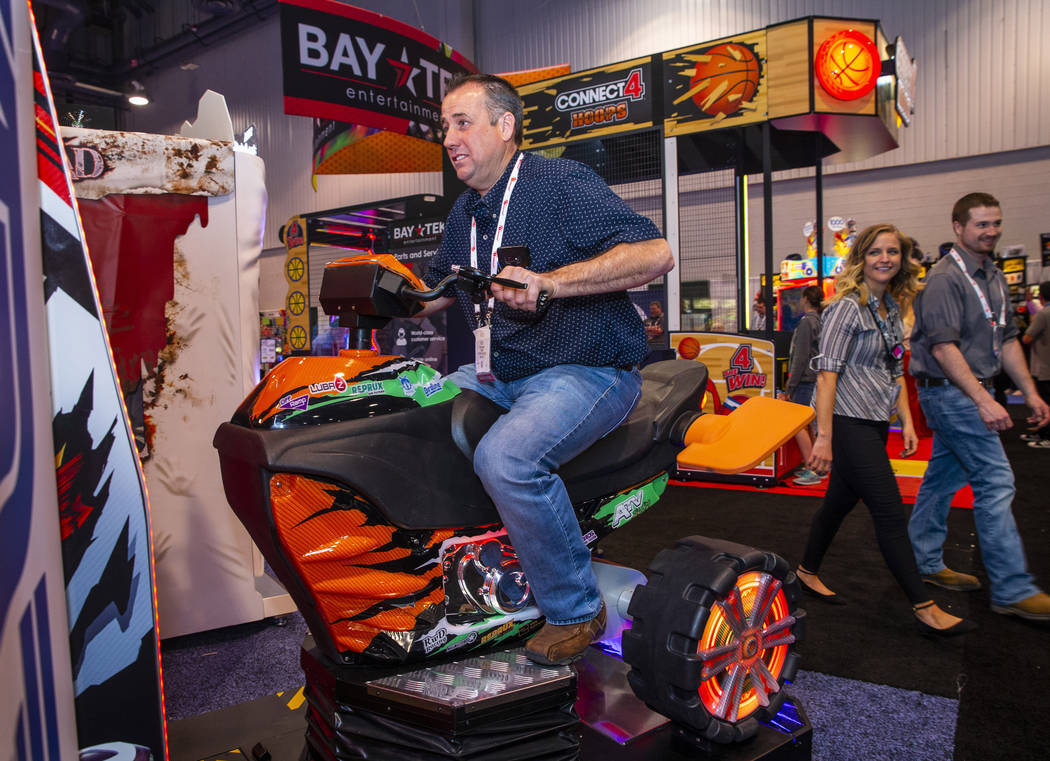 Kyle Pulsifer with Fiddlers Fun Center tests out an ATV driving game during the the Amusement E ...