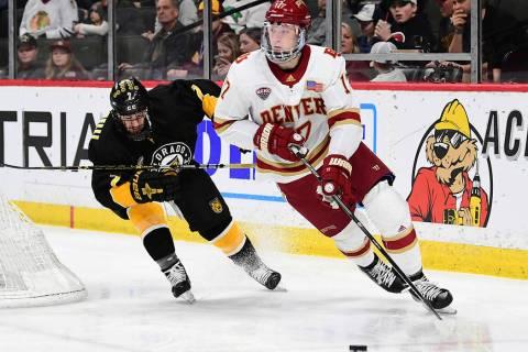Denver Pioneers defenseman Slava Demin (17) is chased by Colorado College Tigers forward Alex B ...