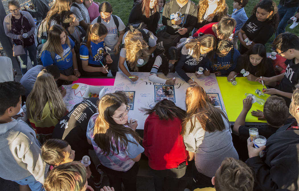 A large group of kids sign a poster honoring the memory of Jonathan Smith, 12, who was struck ...
