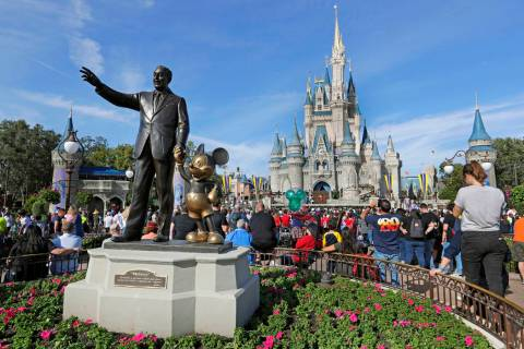 Guests watch a show near a statue of Walt Disney and Micky Mouse in front of the Cinderella Cas ...